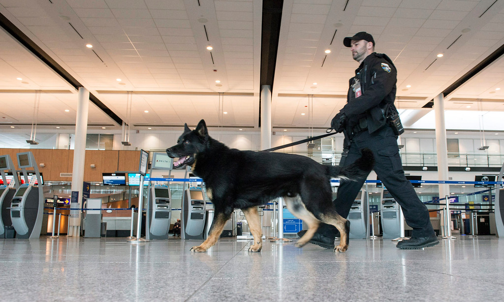 . A police officer and his dog patrols Montreal�Pierre Elliott Trudeau International Airport Tuesday, March 22, 2016 in Montreal. Prime Minister Justin Trudeau condemned Tuesday\'s attacks in Brussels, as his cabinet said they see no imminent threats to Canadians on their soil.  (Paul Chiasson/The Canadian Press via AP)