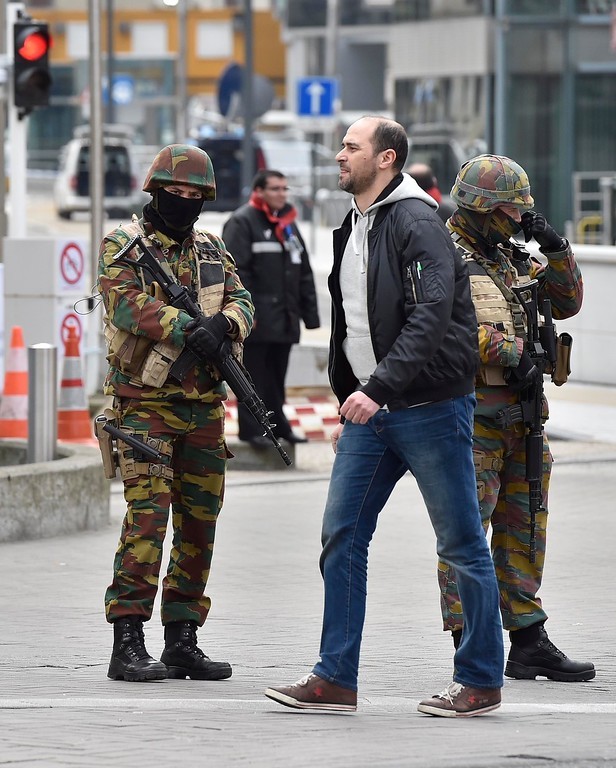 . Security forces secure the city center in Brussels, Belgium, Tuesday, March 22, 2016.  Authorities locked down the Belgian capital on Tuesday after explosions rocked the Brussels airport and subway system, killing  a number of people and injuring many more. Belgium raised its terror alert to its highest level, diverting arriving planes and trains and ordering people to stay where they were. Airports across Europe tightened security. (AP Photo/Martin Meissner)