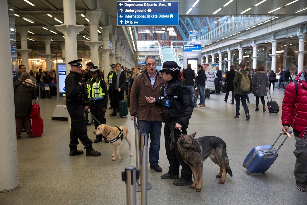 . Police dog handlers speak to travelers as they patrol after Eurostar train services were suspended on the Brussels route because of the attacks in Belgium, at St Pancras international railway station in London, Tuesday, March 22, 2016. Explosions, at least one likely caused by a suicide bomber, rocked the Brussels airport and subway system Tuesday, prompting a lockdown of the Belgian capital and heightened security across Europe. (AP Photo/Matt Dunham)