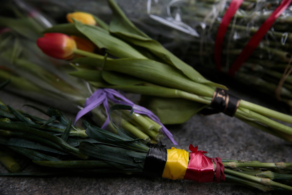 . Flowers wrapped in ribbons in the colours of the Belgium national flag, are placed outside the Belgium Embassy in Moscow, Russia on Tuesday, March 22, 2016. Authorities in Europe have tightened security at airports, on subways, at the borders and on city streets after deadly attacks Tuesday on the Brussels airport and its subway system. (AP Photo/ Pavel Golovkin)