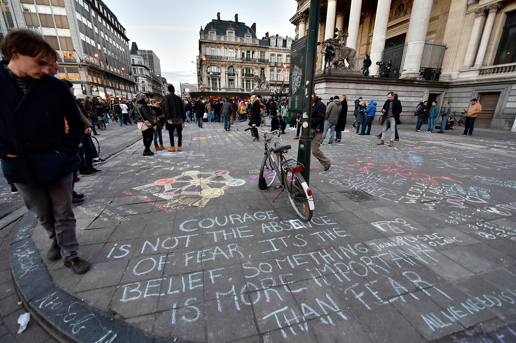 . People write hundreds of messages on the asphalt at Place de la Bourse in the center of Brussels to mourn for the victims of todays attack, Tuesday, March 22, 2016. Bombs exploded at the Brussels airport and one of the city\'s metro stations Tuesday, killing and wounding scores of people, as a European capital was again locked down amid heightened security threats. (AP Photo/Martin Meissner)
