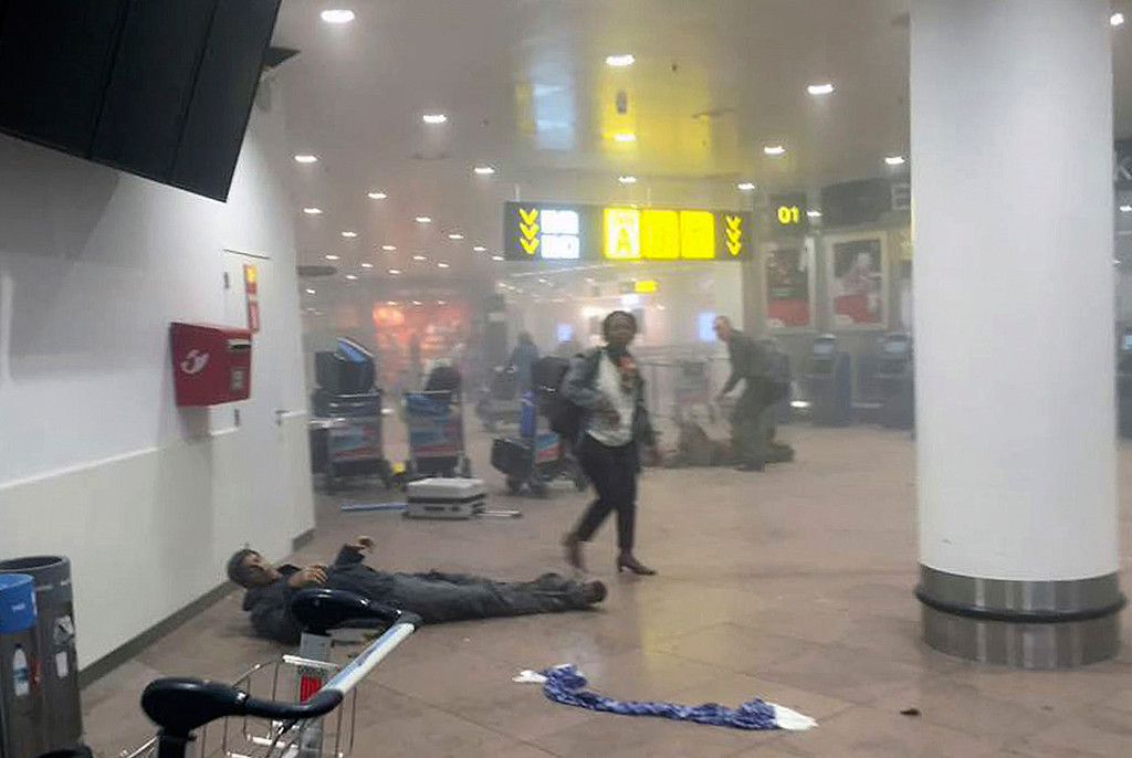 . In this photo provided by Georgian Public Broadcaster and photographed by Ketevan Kardava a man is wounded in Brussels Airport in Brussels, Belgium, after explosions were heard Tuesday, March 22, 2016. A developing situation left a number dead in explosions that ripped through the departure hall at Brussels airport Tuesday, police said. All flights were canceled, arriving planes were being diverted and Belgium\'s terror alert level was raised to maximum, officials said. (Ketevan Kardava/ Georgian Public Broadcaster via AP)