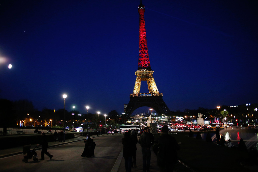 . People walk towards the illuminated Eiffel Tower illuminated with the Belgium national colors black, yellow and red in honor of the victims of the today\'s attacks at the airport and the metro station in Brussels, in Paris, Tuesday, March 22, 2016. Explosions, at least one likely caused by a suicide bomber, rocked the Brussels airport and its subway system Tuesday, prompting a lockdown of the Belgian capital and heightened security across Europe. (AP Photo/Thibault Camus)