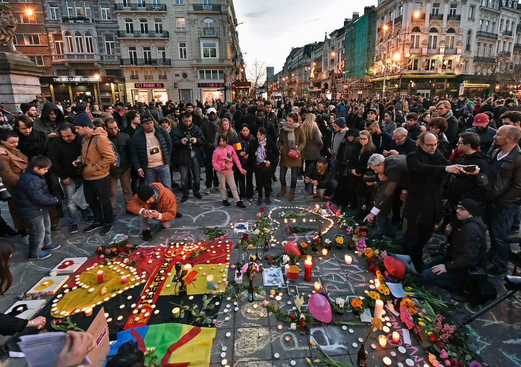 . People bring flowers and candles to mourn at  the Place de la Bourse in the center of Brussels, Tuesday, March 22, 2016. Bombs exploded at the Brussels airport and one of the city\'s metro stations Tuesday, killing and wounding scores of people, as a European capital was again locked down amid heightened security threats. (AP Photo/Martin Meissner)