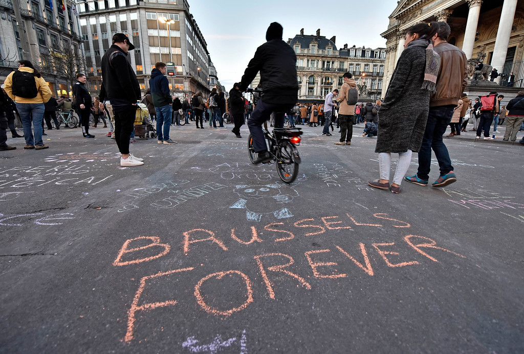 ". A writing on the asphalt reads ""Brussels forever\"" at the place de la Bourse in the center of Brussels, where people write hundreds of messages on the ground to remember the victims of todays attack, Tuesday, March 22, 2016. Bombs exploded at the Brussels airport and one of the city\'s metro stations Tuesday, killing and wounding scores of people, as a European capital was again locked down amid heightened security threats. (AP Photo/Martin Meissner)"
