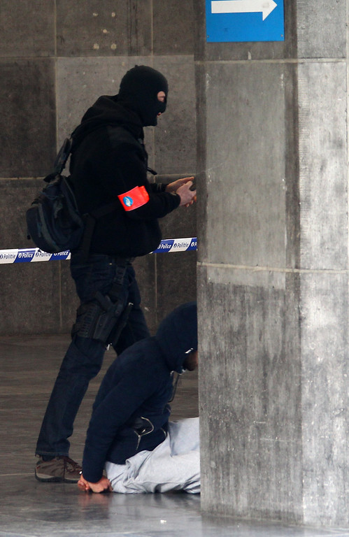 . A Belgian police officer detains a man at the Gare du Midi train station in Brussels, Tuesday, March 22, 2016. Explosions, at least one likely caused by a suicide bomber, rocked the Brussels airport and its subway system Tuesday, prompting a lockdown of the Belgian capital and heightened security across Europe. (AP Photo/Michel Spingler)