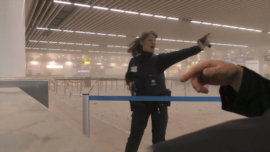 . In this photo provided by Ralph Usbeck a police officers directs passengers in a smoke filled terminal at Brussels Airport, in Brussels after explosions Tuesday, March 22, 2016. Authorities locked down the Belgian capital on Tuesday after explosions rocked the Brussels airport and subway system, killing  a number of people and injuring many more. Belgium raised its terror alert to its highest level, diverting arriving planes and trains and ordering people to stay where they were. Airports across Europe tightened security.  (Ralph Usbeck via AP)