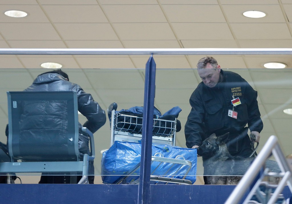 . A police officer with a sniffer dog checks  luggage at the airport in Prague, Czech Republic, Tuesday, March 22, 2016.  Authorities in Europe have tightened security at airports, on subways, at the borders and on city streets after deadly attacks Tuesday on the Brussels airport and its subway system. (AP Photo/Petr David Josek)