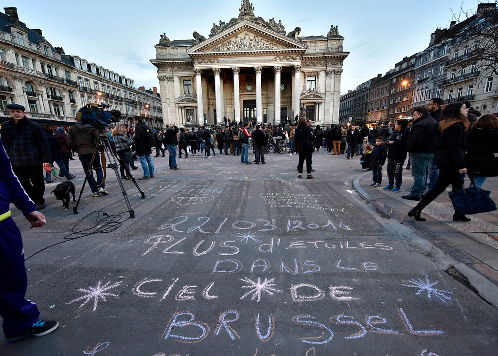 ". Writing on the asphalt reads ""More stars in Brussel\'s heaven\"" at Place de la Bourse in the center of Brussels, where people write hundreds of messages on the ground to remember the victims of Tuesday\'s attack, Tuesday, March 22, 2016. Bombs exploded at the Brussels airport and one of the city\'s metro stations Tuesday, killing and wounding scores of people, as a European capital was again locked down amid heightened security threats. (AP Photo/Martin Meissner)"