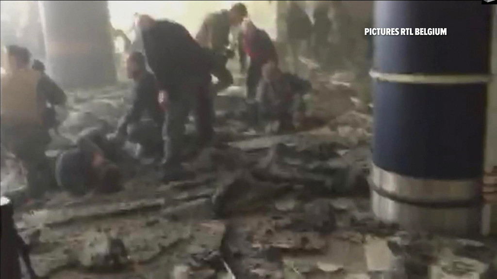 . In this still image taken from video from RTL Belgium  people receive treatment in the debris strewn terminal at Brussels Airport, in Brussels after explosions Tuesday, March 22, 2016. Authorities locked down the Belgian capital on Tuesday after explosions rocked the Brussels airport and subway system, killing  a number of people and injuring many more. Belgium raised its terror alert to its highest level, diverting arriving planes and trains and ordering people to stay where they were. Airports across Europe tightened security.  (RTL via AP)
