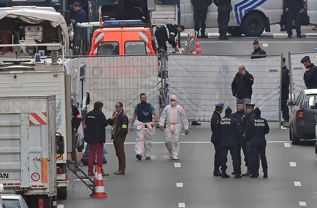 . Forensic staff leave metro station Maelbeek in Brussels, Tuesday, March 22, 2016. Explosions, at least one likely caused by a suicide bomber, rocked the Brussels airport and its subway system Tuesday, prompting a lockdown of the Belgian capital and heightened security across Europe. (AP Photo/Martin Meissner)