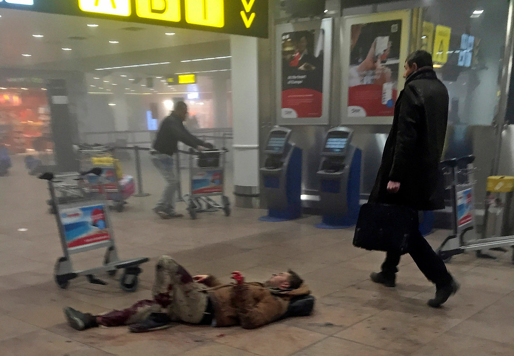 . In this photo provided by Georgian Public Broadcaster and photographed by Ketevan Kardava, an injured man lies on the floor in Brussels Airport in Brussels, Belgium, after explosions were heard Tuesday, March 22, 2016. A developing situation left a number dead in explosions that ripped through the departure hall at Brussels airport Tuesday, police said. All flights were canceled, arriving planes were being diverted and Belgium\'s terror alert level was raised to maximum, officials said. (Ketevan Kardava/ Georgian Public Broadcaster via AP)