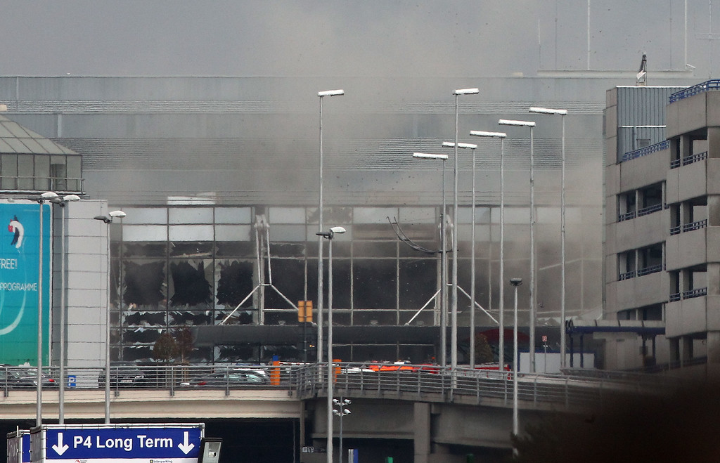 . Smoke billows from the  Zaventem Airport after a controlled explosion in Brussels, Tuesday, March 22, 2016. Bombs struck the Brussels airport and one of the city\'s metro stations Tuesday, killing and wounding dozens of people, as a European capital was again locked down amid heightened security threats. (AP Photo/Michel Spingler)