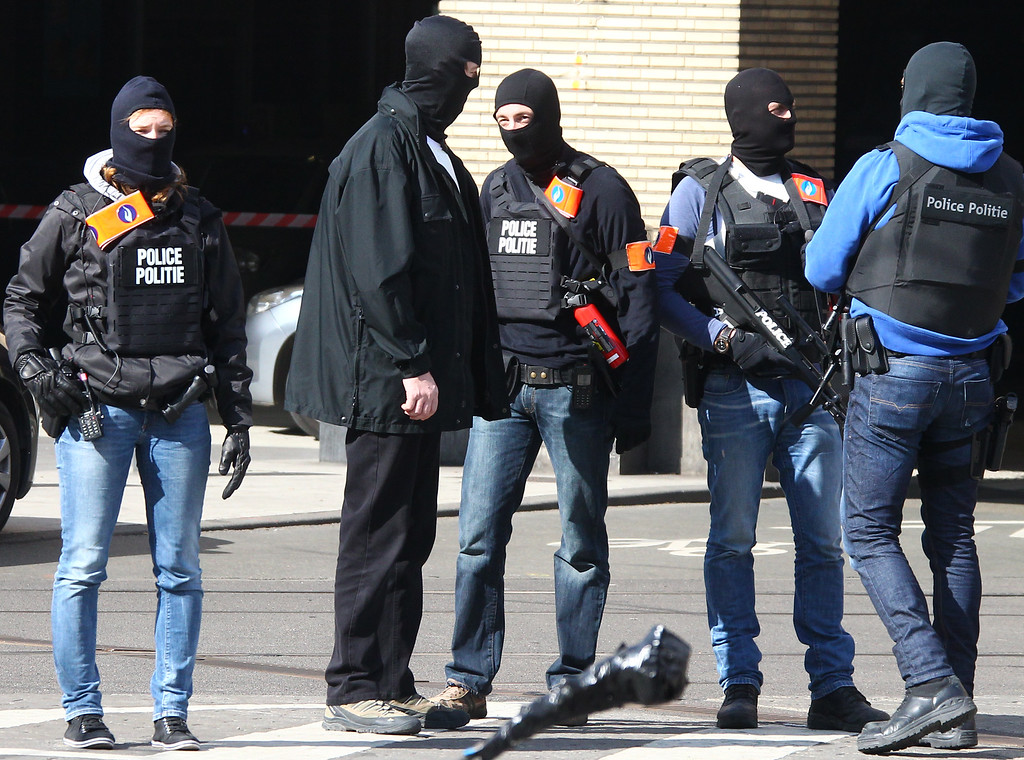 . Hooded Belgian police officers patrol outside the Gare du Midi train station in Brussels, Tuesday, March 22, 2016. Explosions, at least one likely caused by a suicide bomber, rocked the Brussels airport and its subway system Tuesday, prompting a lockdown of the Belgian capital and heightened security across Europe. (AP Photo/Michel Spingler)