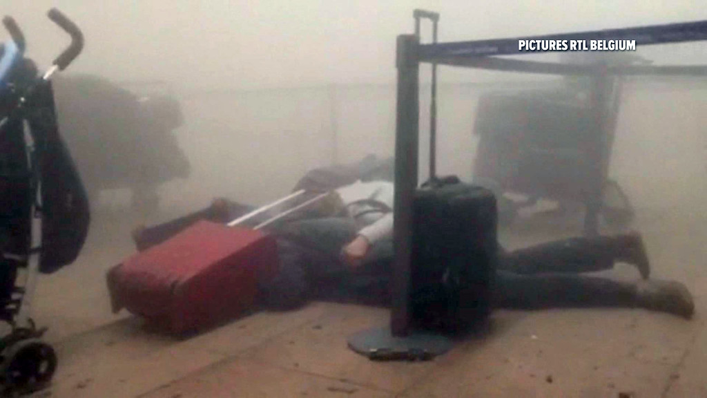 . In this still image taken from video from RTL Belgium  unidentified travellers lie on the floor in a smoke filled terminal at Brussels Airport, in Brussels after explosions Tuesday, March 22, 2016. Authorities locked down the Belgian capital on Tuesday after explosions rocked the Brussels airport and subway system, killing  a number of people and injuring many more. Belgium raised its terror alert to its highest level, diverting arriving planes and trains and ordering people to stay where they were. Airports across Europe tightened security.  (RTL via AP)