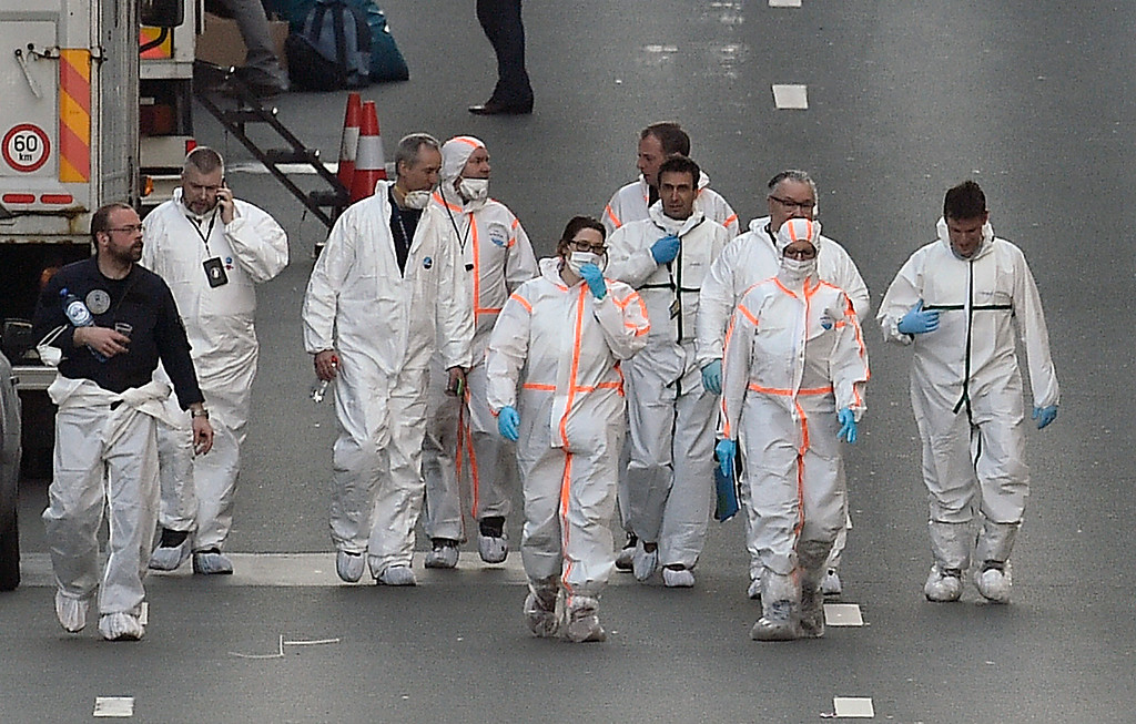 . Forensic staff leave the metro station Maelbeek in Brussels, Tuesday, March 22, 2016. Explosions, at least one likely caused by a suicide bomber, rocked the Brussels airport and its subway system Tuesday, prompting a lockdown of the Belgian capital and heightened security across Europe. (AP Photo/Martin Meissner)