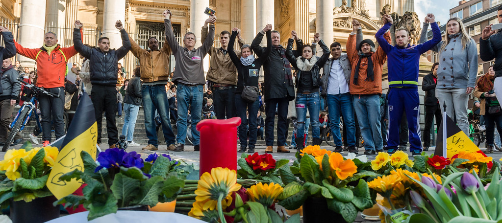 . People hold hands in solidarity near a memorial to attack victims outside the stock exchange in Brussels on Tuesday, March 22, 2016. Explosions, at least one likely caused by a suicide bomber, rocked the Brussels airport and subway system Tuesday, prompting a lockdown of the Belgian capital and heightened security across Europe. (AP Photo/Geert Vanden Wijngaert)