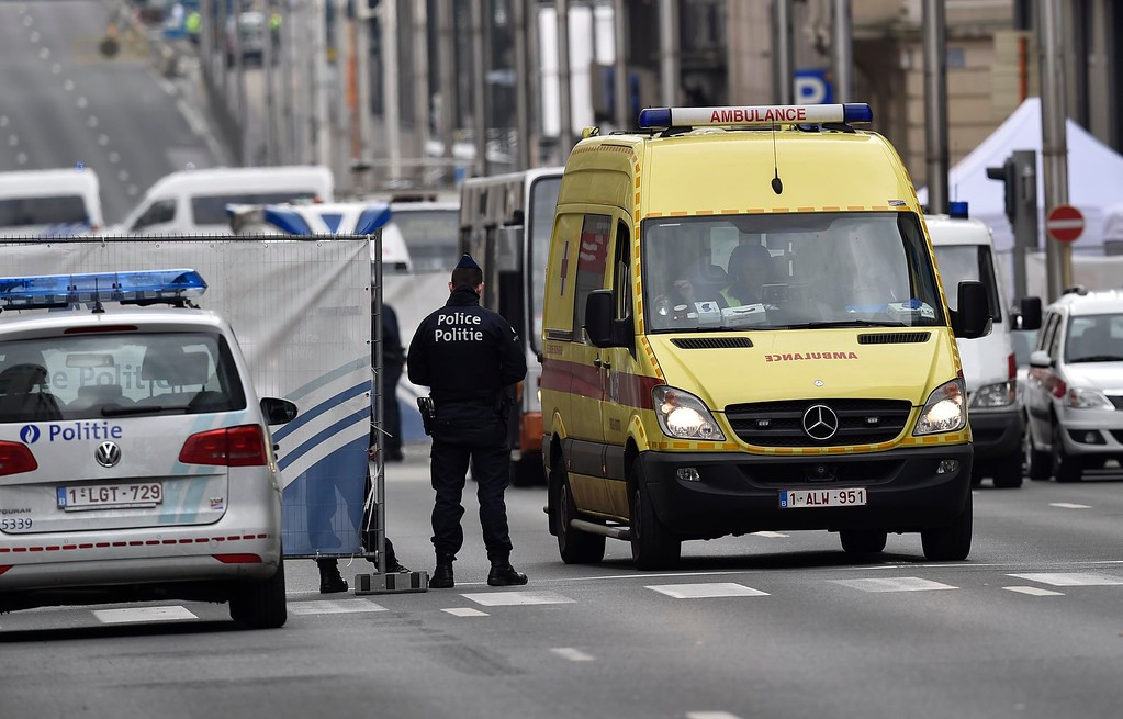 . A ambulance leaves the metro station, closed by police, in Brussels, Belgium, Tuesday, March 22, 2016.  Authorities locked down the Belgian capital on Tuesday after explosions rocked the Brussels airport and subway system, killing  a number of people and injuring many more. Belgium raised its terror alert to its highest level, diverting arriving planes and trains and ordering people to stay where they were. Airports across Europe tightened security. (AP Photo/Martin Meissner)