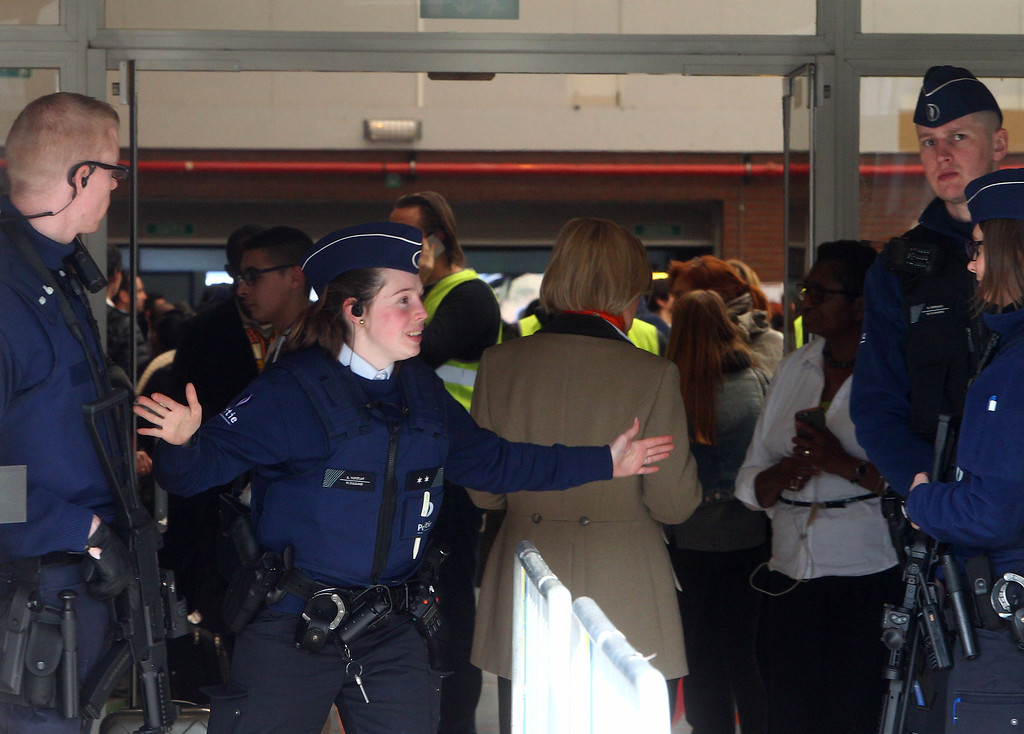 . A police officer gestures outside a gym where passengers took shelter after the explosions, near  the  Zaventem Airport in Brussels, Tuesday, March 22, 2016. Bombs struck the Brussels airport and one of the city\'s metro stations Tuesday, killing and wounding dozens of people, as a European capital was again locked down amid heightened security threats. (AP Photo/Michel Spingler)