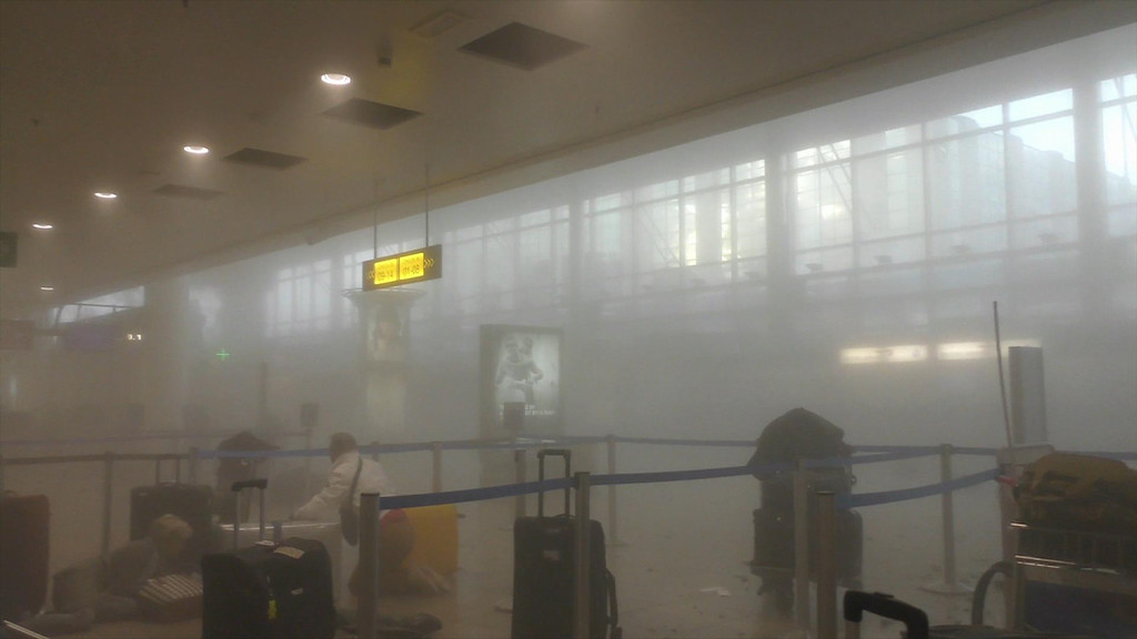 . In this photo provided by Ralph Usbeck an unidentified traveller gets to his feet in a smoke filled terminal at Brussels Airport, in Brussels after explosions Tuesday, March 22, 2016. Authorities locked down the Belgian capital on Tuesday after explosions rocked the Brussels airport and subway system, killing  a number of people and injuring many more. Belgium raised its terror alert to its highest level, diverting arriving planes and trains and ordering people to stay where they were. Airports across Europe tightened security.  (Ralph Usbeck via AP)