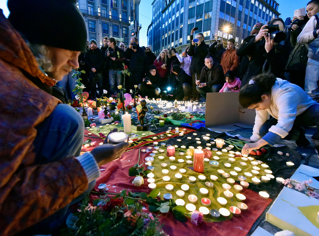 . People bring flowers and candles to mourn for the victims at Place de la Bourse in the center of Brussels, Tuesday, March 22, 2016. Bombs exploded at the Brussels airport and one of the city\'s metro stations Tuesday, killing and wounding scores of people, as a European capital was again locked down amid heightened security threats. (AP Photo/Martin Meissner)
