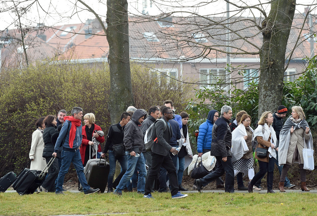 . People walk across a field as they are evacuated from Zaventem Airport in Brussels after an explosion on Tuesday, March 22, 2016. Explosions, at least one likely caused by a suicide bomber, rocked the Brussels airport and subway system Tuesday, prompting a lockdown of the Belgian capital and heightened security across Europe. At least 26 people were reported dead. (AP Photo/Geert Vanden Wijngaert)