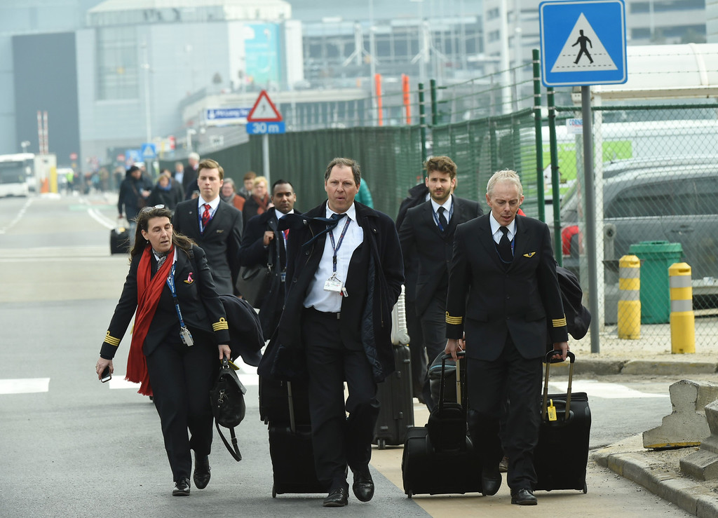 . A pilot and cabin crew are evacuated from Zaventem Airport in Brussels by bus after an explosion on Tuesday, March 22, 2016. Explosions, at least one likely caused by a suicide bomber, rocked the Brussels airport and subway system Tuesday, prompting a lockdown of the Belgian capital and heightened security across Europe. At least 26 people were reported dead. (AP Photo/Geert Vanden Wijngaert)