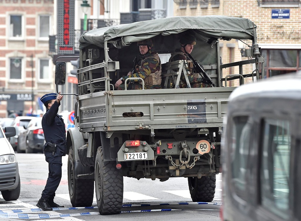 . Police and military secure the city center in Brussels, Belgium, Tuesday, March 22, 2016.  Authorities locked down the Belgian capital on Tuesday after explosions rocked the Brussels airport and subway system, killing  a number of people and injuring many more. Belgium raised its terror alert to its highest level, diverting arriving planes and trains and ordering people to stay where they were. Airports across Europe tightened security. (AP Photo/Martin Meissner)