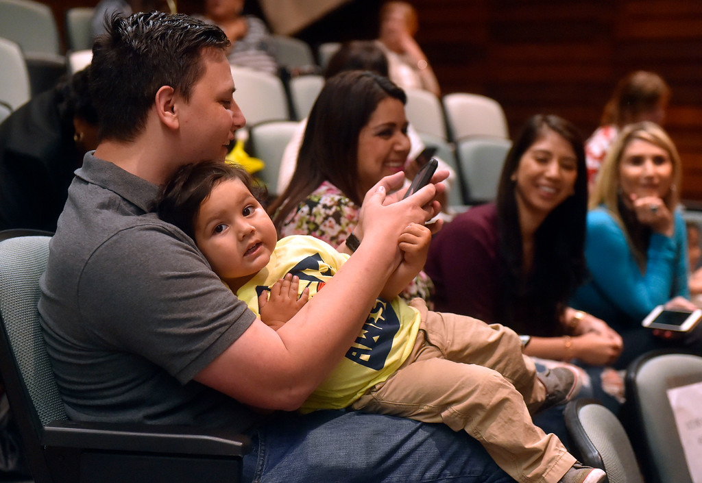 . Two-year-old Alexander Godoy squirms in his father James Godoy�s lap as they wait for his late-mother to be honored at L.A. Harbor College in Harbor City, CA on Wednesday, May 11, 2016. On Wednesday, LAHC officials posthumously awarded an Associate Degree in Liberal Arts and Sciences to Aurora Godoy. Godoy, who was killed in the San Bernardino terror attack in December, was two classes shy of earning her degree. (Photo by Scott Varley, Daily Breeze)