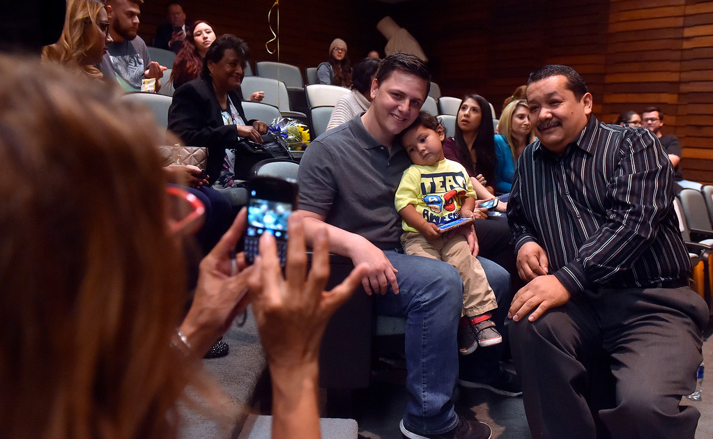 . James Godoy holds his 2-year-old son Alexander as he poses for a photo with his father-in-law Juan Banales at L.A. Harbor College in Harbor City, CA on Wednesday, May 11, 2016. On Wednesday, LAHC officials posthumously awarded an Associate Degree in Liberal Arts and Sciences to Aurora Godoy. Godoy, who was killed in the San Bernardino terror attack in December, was two classes shy of earning her degree. (Photo by Scott Varley, Daily Breeze)