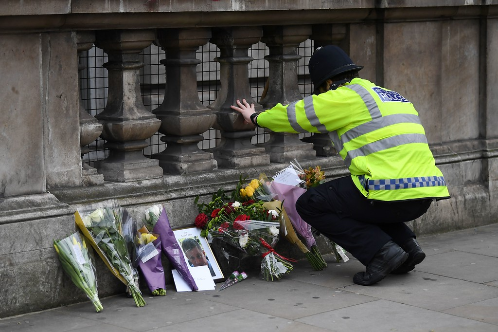 . A police officer lays flowers on Whitehall around a photograph of police officer Keith Palmer who was killed in the March 22 terror attack in Westminster, in Westminster near the Houses of the Parliament in central London on March 23, 2017.  Britain\'s parliament reopened on Thursday with a minute\'s silence in a gesture of defiance a day after an attacker sowed terror in the heart of Westminster, killing three people before being shot dead. Sombre-looking lawmakers in a packed House of Commons chamber bowed their heads and police officers also marked the silence standing outside the headquarters of London\'s Metropolitan Police nearby. (JUSTIN TALLIS/AFP/Getty Images)