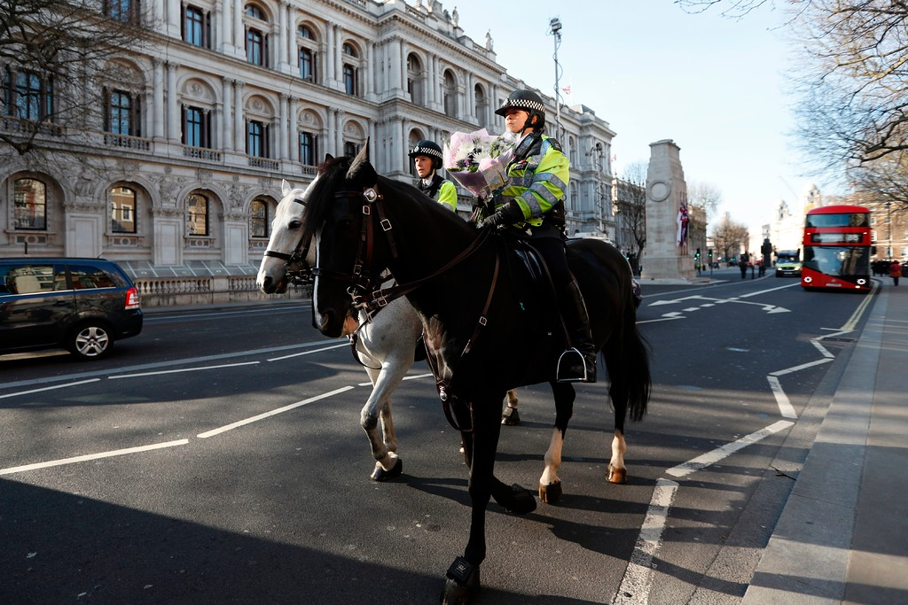 ". A mounted police officer carries a bunch of flowers to lay at the gates of the Houses of Parliament in central London on March 24, 2017 two days after the March 22 terror attack on the British parliament and Westminster Bridge. British police said on March 24 they had made two further ""significant\"" arrests over the Islamist-inspired terror attack on parliament, as they appealed for information about the homegrown killer who left four people dead. Nine people are now in custody over the March 22 rampage in Westminster, in which at least 50 people were injured, 31 requiring hospital treatment, counter-terrorism commander Mark Rowley said. (ADRIAN DENNIS/AFP/Getty Images)"
