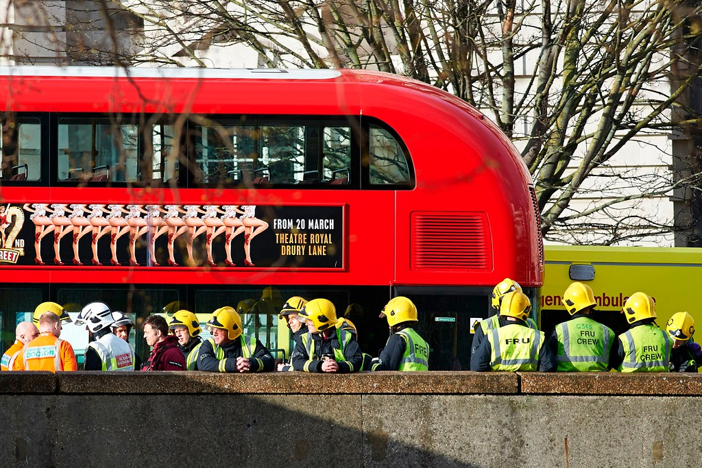 . Members of the Ambulance and Fire Brigade emergency services stand alongside a stationary London bus as they work on Westminster Bridge, alongside the Houses of Parliament in central London on March 22, 2017 during an emergency incident. Britain\'s Houses of Parliament were in lockdown on Wednesday after staff said they heard shots fired, triggering a security alert. (NIKLAS HALLE\'N/AFP/Getty Images)