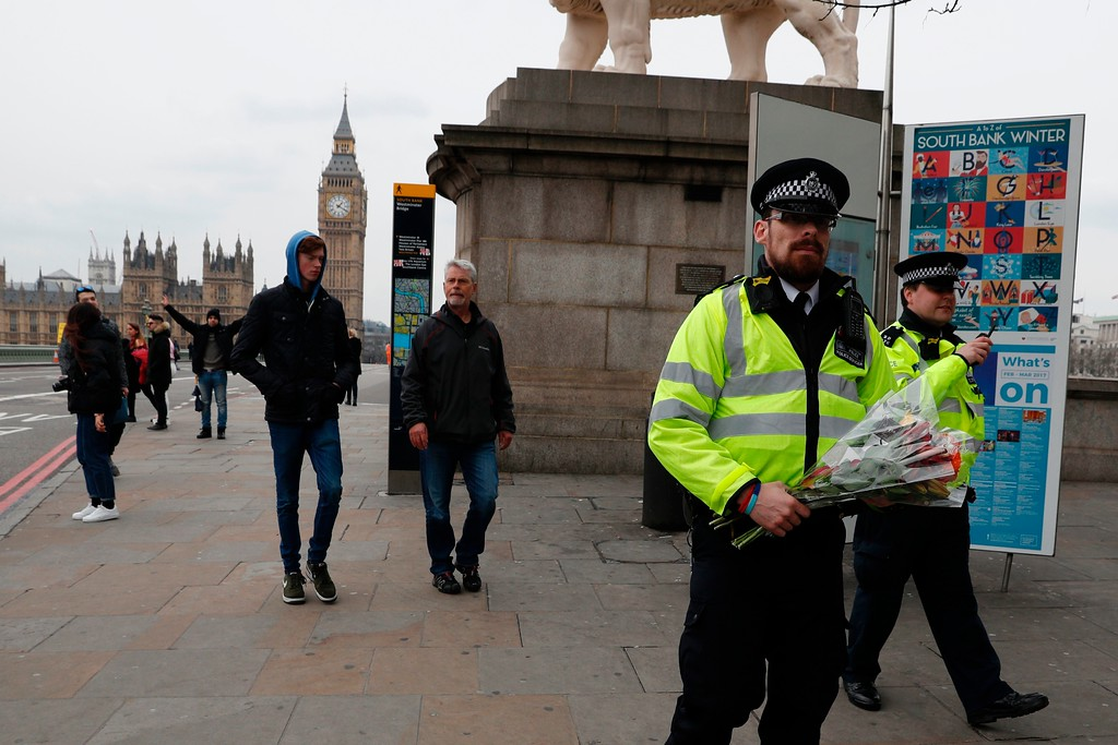 . A police officer carries a bunch of flowers as pedestrians cross Westminster Bridge with the Houses of Parliament in the background in central London on March 23, 2017 after it reopened following its closure by security services during and after the March 22 terror attack.  Britain\'s parliament reopened on Thursday with a minute\'s silence in a gesture of defiance a day after an attacker sowed terror in the heart of Westminster, killing three people before being shot dead. Sombre-looking lawmakers in a packed House of Commons chamber bowed their heads and police officers also marked the silence standing outside the headquarters of London\'s Metropolitan Police nearby. (ADRIAN DENNIS/AFP/Getty Images)