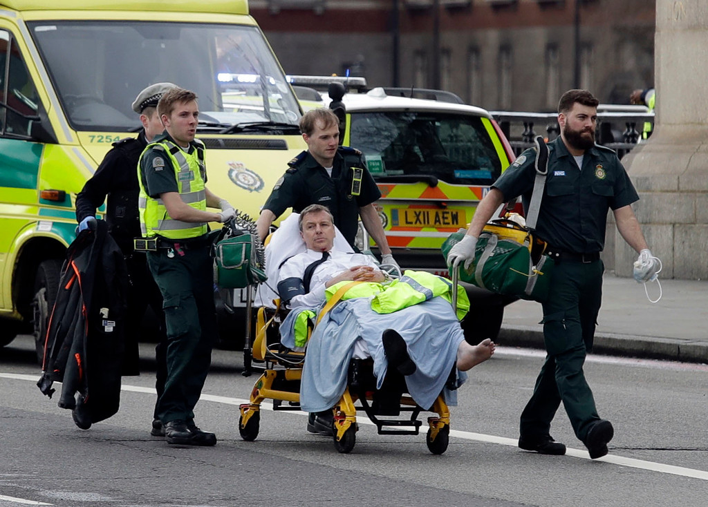 ". Emergency services transport an injured person to an ambulance, close to the Houses of Parliament in London, Wednesday, March 22, 2017. London police say they are treating a gun and knife incident at Britain\'s Parliament ""as a terrorist incident until we know otherwise.\"" The Metropolitan Police says in a statement that the incident is ongoing. Officials say a man with a knife attacked a police officer at Parliament and was shot by officers. Nearby, witnesses say a vehicle struck several people on the Westminster Bridge.  (AP Photo/Matt Dunham)"