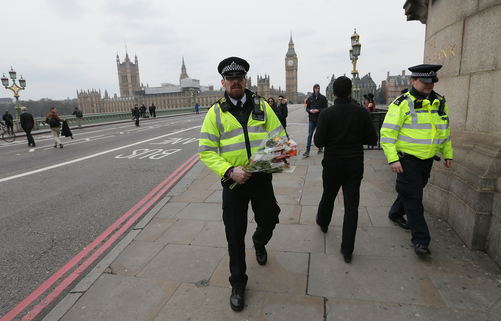 ". A police officer carries a flower tribute as Westminster Bridge is re-opened to the public Thursday, March 23, 2017, following an attack on Wednesday when a man drove a car into pedestrians then stabbed a police officer to death before being fatally shot by police within Parliament\'s grounds.  The IS-linked Aamaq news agency said Thursday that the person who carried out the ""attack in front of the British parliament in London was a soldier of the Islamic State.\"" (AP Photo/Tim Ireland)"