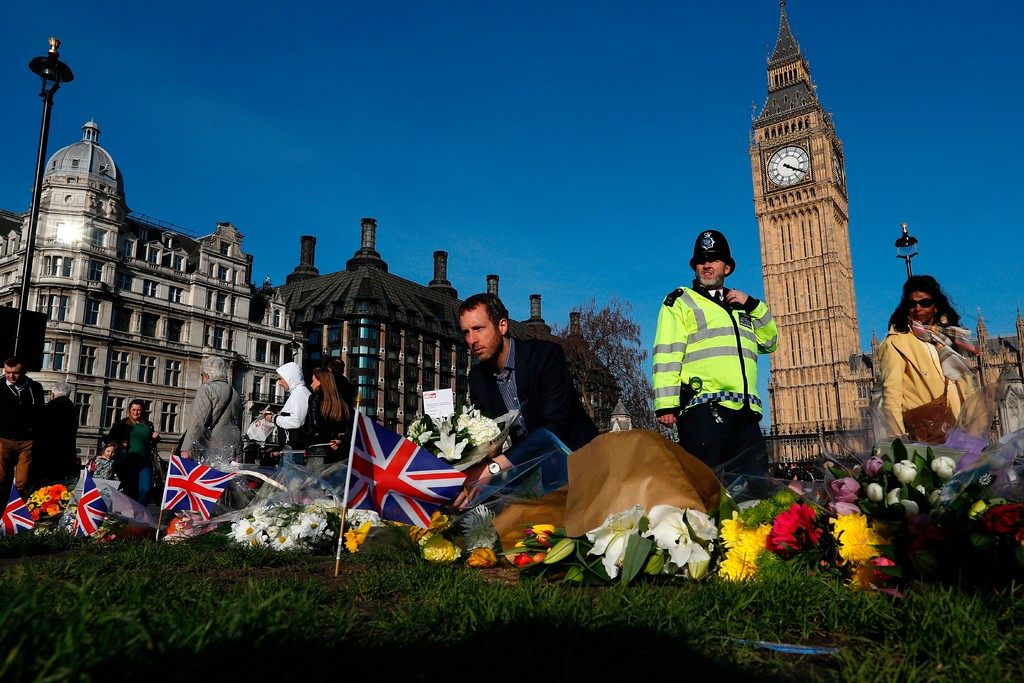 ". People lay floral tributes to the victims of the March 22 terror attack in Parliament Square outside the Houses of Parliament in central London on March 24, 2017.  British police said on March 24 they had made two further ""significant\"" arrests over the Islamist-inspired terror attack on parliament, as they appealed for information about the homegrown killer who left four people dead. Nine people are now in custody over the March 22 rampage in Westminster, in which at least 50 people were injured, 31 requiring hospital treatment, counter-terrorism commander Mark Rowley said. (ADRIAN DENNIS/AFP/Getty Images)"