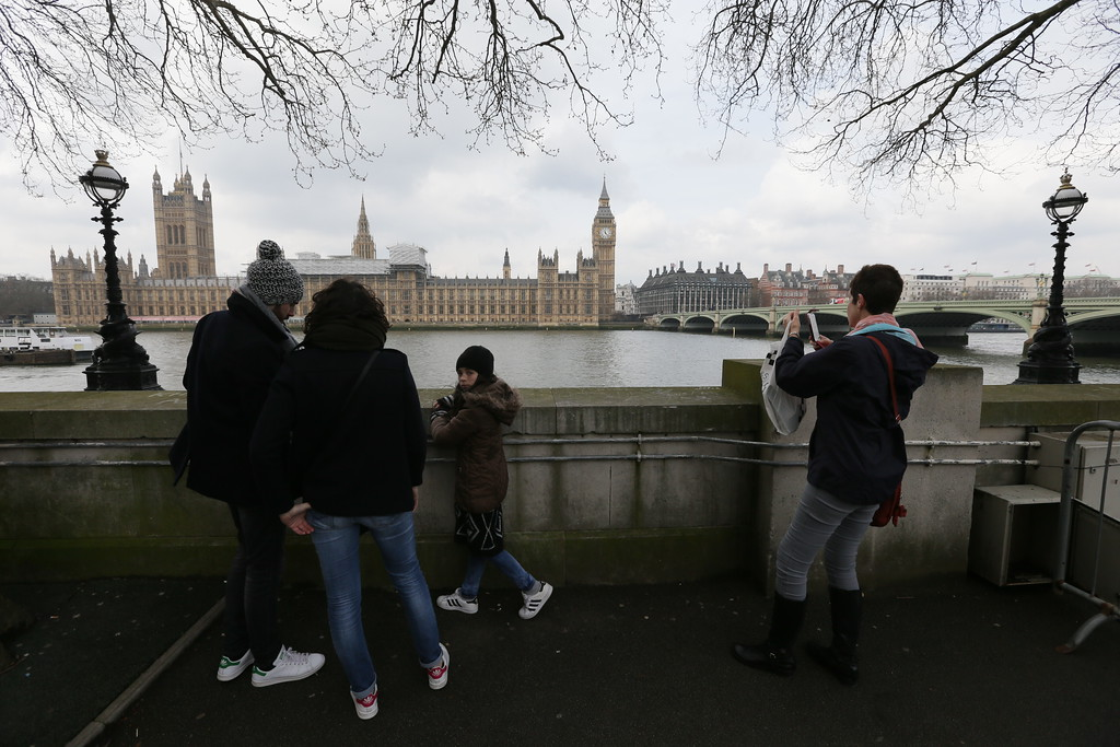 . Tourists view parliament from across the River Thames, with Westminster Bridge, right, in London, Thursday March 23, 2017, the scene of an attack.  On Wednesday a knife-wielding man went on a deadly rampage, first driving a car into pedestrians then stabbing a police officer to death before being fatally shot by police within Parliament\'s grounds in London.  (AP Photo/Tim Ireland)