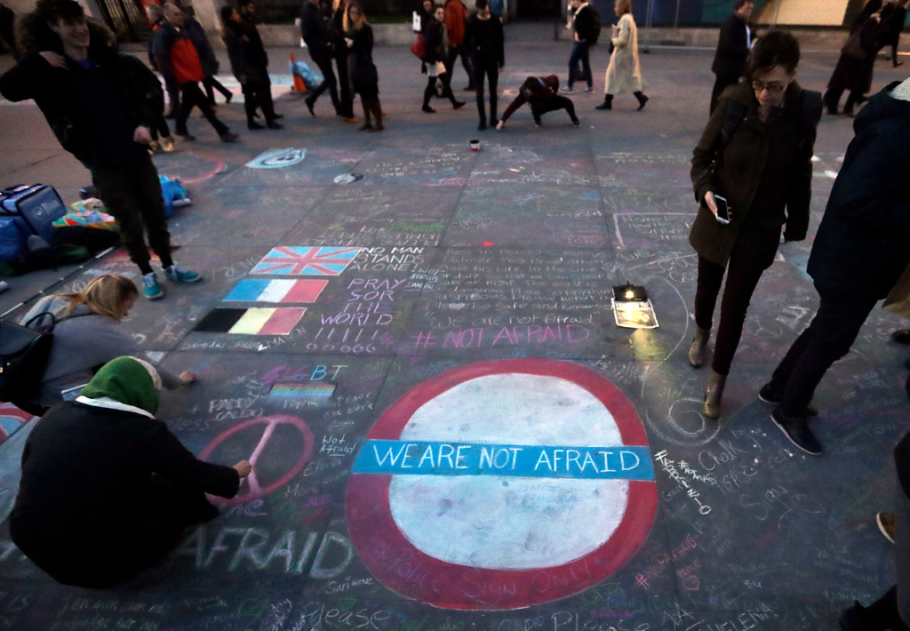 . People write messages in chalk on the ground at a vigil for the victims of Wednesday\'s attack, at Trafalgar Square in London, Thursday, March 23, 2017. The Islamic State group has claimed responsibility for an attack by a man who plowed an SUV into pedestrians and then stabbed a police officer to death on the grounds of Britain\'s Parliament. Mayor Sadiq Khan called for Londoners to attend a candlelit vigil at Trafalgar Square on Thursday evening in solidarity with the victims and their families and to show that London remains united. (AP Photo/Matt Dunham)