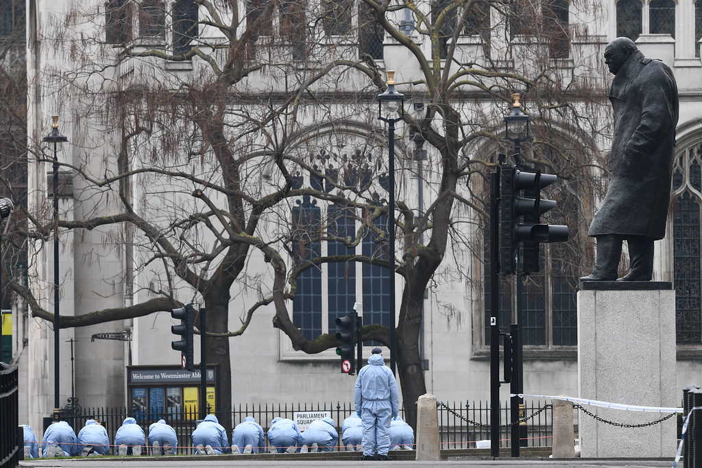 . Police in forensic suits search Parliament Square outside the Houses of Parliament in central London on March 23, 2017 the day after the March 22 terror attack in Westminster claimed at least three lives including that of police officer Keith Palmer.  Britain\'s parliament reopened on Thursday with a minute\'s silence in a gesture of defiance a day after an attacker sowed terror in the heart of Westminster, killing three people before being shot dead. Sombre-looking lawmakers in a packed House of Commons chamber bowed their heads and police officers also marked the silence standing outside the headquarters of London\'s Metropolitan Police nearby. (JUSTIN TALLIS/AFP/Getty Images)