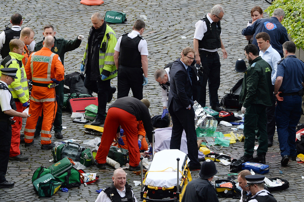 ". Conservative MP Tobias Ellwood, centre, stands amongst the emergency services at the scene outside the Palace of Westminster, London, Wednesday, March 22, 2017.  London police say they are treating a gun and knife incident at Britain\'s Parliament ""as a terrorist incident until we know otherwise.\"" The Metropolitan Police says in a statement that the incident is ongoing. It is urging people to stay away from the area. Officials say a man with a knife attacked a police officer at Parliament and was shot by officers. Nearby, witnesses say a vehicle struck several people on the Westminster Bridge.  (Stefan Rousseau/PA via AP)."