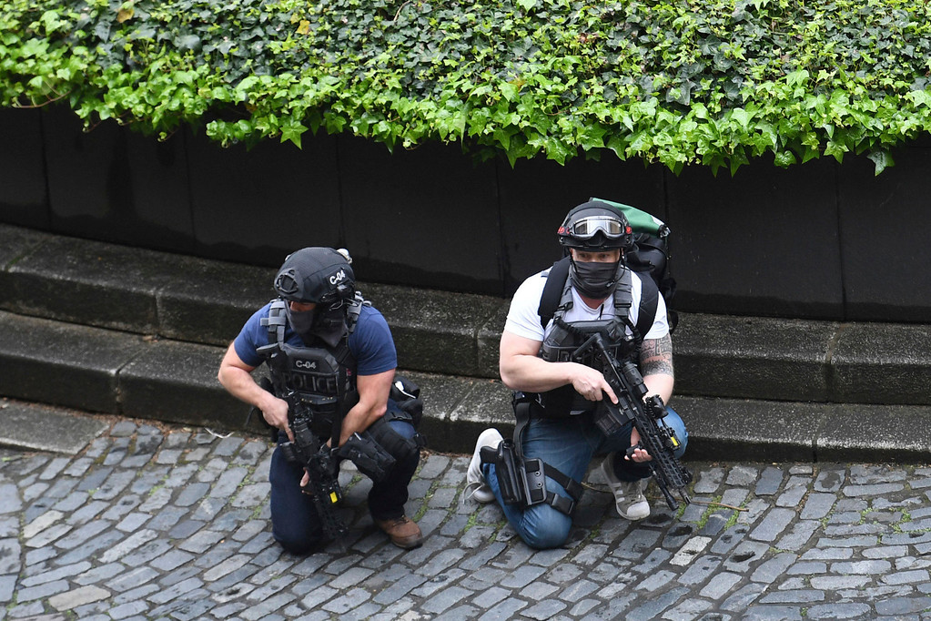 ". Armed police outside the the Houses of Parliament, London, Wednesday, March 22, 2017.  London police say they are treating a gun and knife incident at Britain\'s Parliament ""as a terrorist incident until we know otherwise.\"" The Metropolitan Police says in a statement that the incident is ongoing. It is urging people to stay away from the area. Officials say a man with a knife attacked a police officer at Parliament and was shot by officers. Nearby, witnesses say a vehicle struck several people on the Westminster Bridge.  (Stefan Rousseau/PA via AP)."