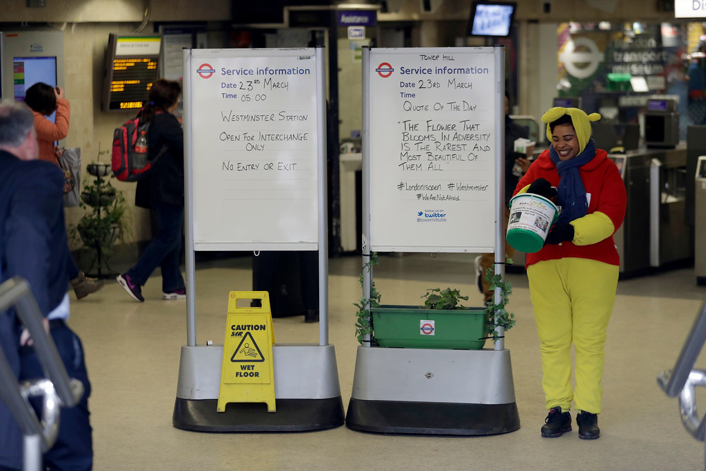 ". A woman collecting money for charity stands next to a quote written on an information board at Tower Hill underground train station, written in defiance of the previous day\'s attack in London, Thursday, March 23, 2017.  The IS-linked Aamaq news agency said Thursday that the person who carried out the ""attack in front of the British parliament in London was a soldier of the Islamic State.\"" (AP Photo/Matt Dunham)"