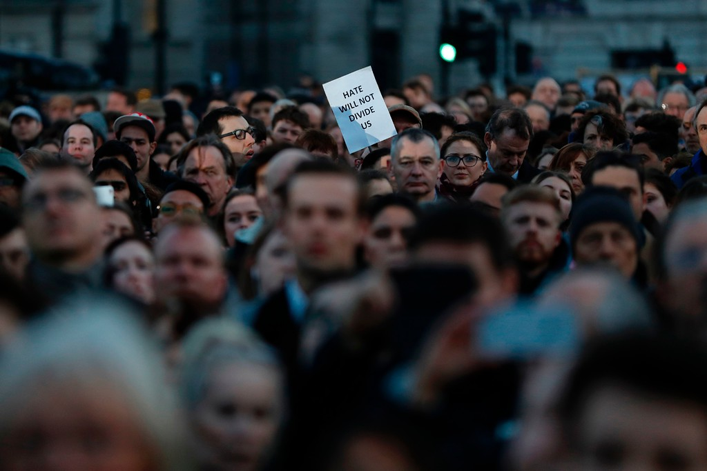 ". A member of the public holds up a sign reading ""hate will not divide us\"" during a vigil in Trafalgar Square in central London on March 23, 2017 in solidarity with the victims of the March 22 terror attack at the British parliament and on Westminster Bridge.  Britain\'s parliament reopened on Thursday with a minute\'s silence in a gesture of defiance a day after an attacker sowed terror in the heart of Westminster, killing three people before being shot dead. Sombre-looking lawmakers in a packed House of Commons chamber bowed their heads and police officers also marked the silence standing outside the headquarters of London\'s Metropolitan Police nearby. (ADRIAN DENNIS/AFP/Getty Images)"