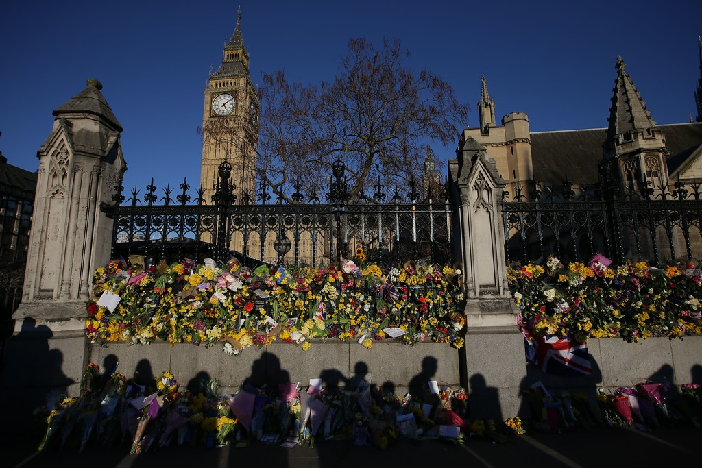 . The shadows of onlookers are cast on floral tributes to the victims of the March 22 terror attack pushed through the railings of the Houses of Parliament in central London on March 25, 2017.   (DANIEL LEAL-OLIVAS/AFP/Getty Images)
