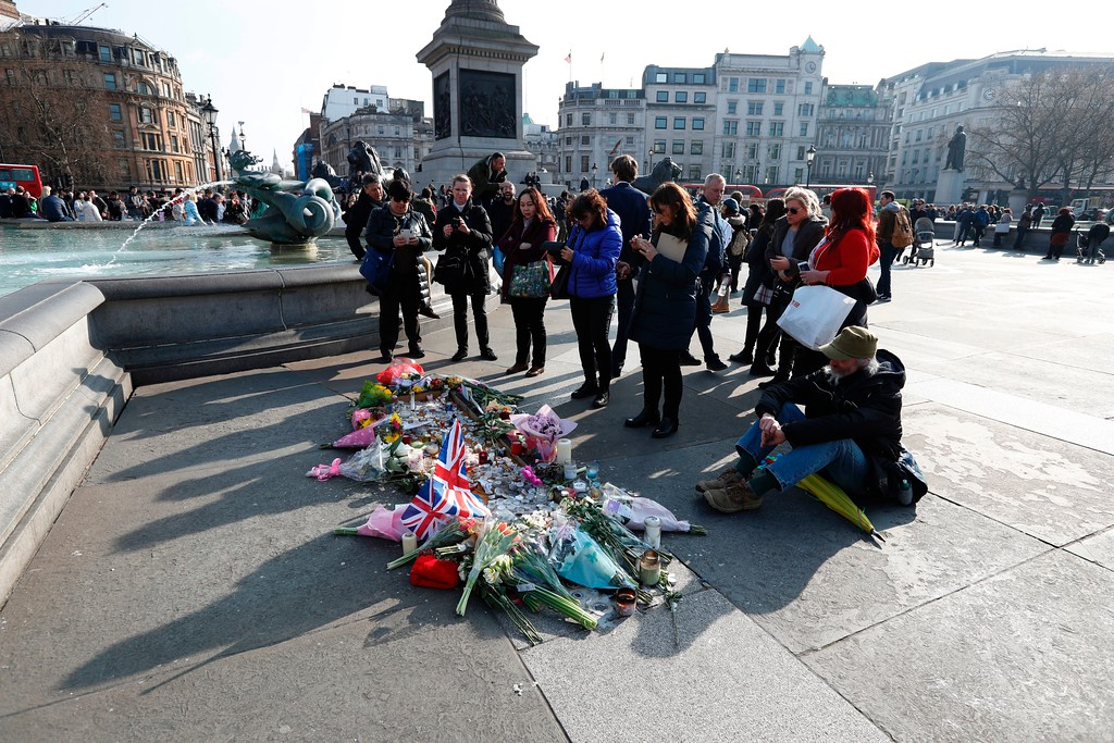 ". A man sits beside a small memorial and floral tributes to the victims of the March 22 terror attack on the British Parliament and Westminster Bridge in Trafalgar Square in central London on March 24, 2017.  British police said on March 24 they had made two further ""significant\"" arrests over the Islamist-inspired terror attack on parliament, as they appealed for information about the homegrown killer who left four people dead. Nine people are now in custody over the March 22 rampage in Westminster, in which at least 50 people were injured, 31 requiring hospital treatment, counter-terrorism commander Mark Rowley said. (ADRIAN DENNIS/AFP/Getty Images)"