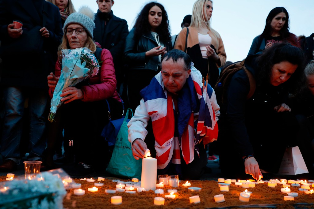 . People including a man draped in the Union Flag, John Loughrey (C), light candles on a patch of sand during a vigil in Trafalgar Square in central London on March 23, 2017 in solidarity with the victims of the March 22 terror attack at the British parliament and on Westminster Bridge.  Britain\'s parliament reopened on Thursday with a minute\'s silence in a gesture of defiance a day after an attacker sowed terror in the heart of Westminster, killing three people before being shot dead. Sombre-looking lawmakers in a packed House of Commons chamber bowed their heads and police officers also marked the silence standing outside the headquarters of London\'s Metropolitan Police nearby. (ADRIAN DENNIS/AFP/Getty Images)