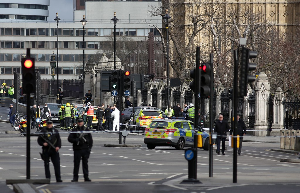 ". Armed police officers stand guard as forensics officers work around a grey vehicle that crashed into the railings of the Houses of Parliament in central London on March 22, 2017, during an emergency incident. British police shot a suspected attacker outside the Houses of Parliament in London on Wednesday after an officer was stabbed in what police said was a ""terrorist\"" incident. One woman has died and others have \""catastrophic\"" injuries following a suspected terror attack outside the British parliament, local media reported on Wednesday citing a junior doctor. (DANIEL LEAL-OLIVAS/AFP/Getty Images)"