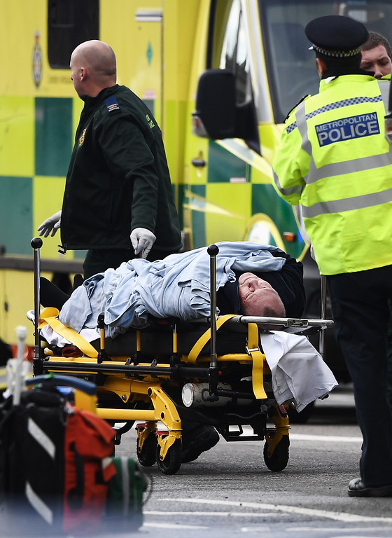 . LONDON, ENGLAND - MARCH 22:  A member of the public is treated by emergency services near Westminster Bridge and the Houses of Parliament on March 22, 2017 in London, England. A police officer was stabbed near to the British Parliament and the alleged assailant shot by armed police. Scotland Yard also reported an incident on Westminster Bridge where one woman has been killed and several people seriously injured by a car.  (Photo by Carl Court/Getty Images)
