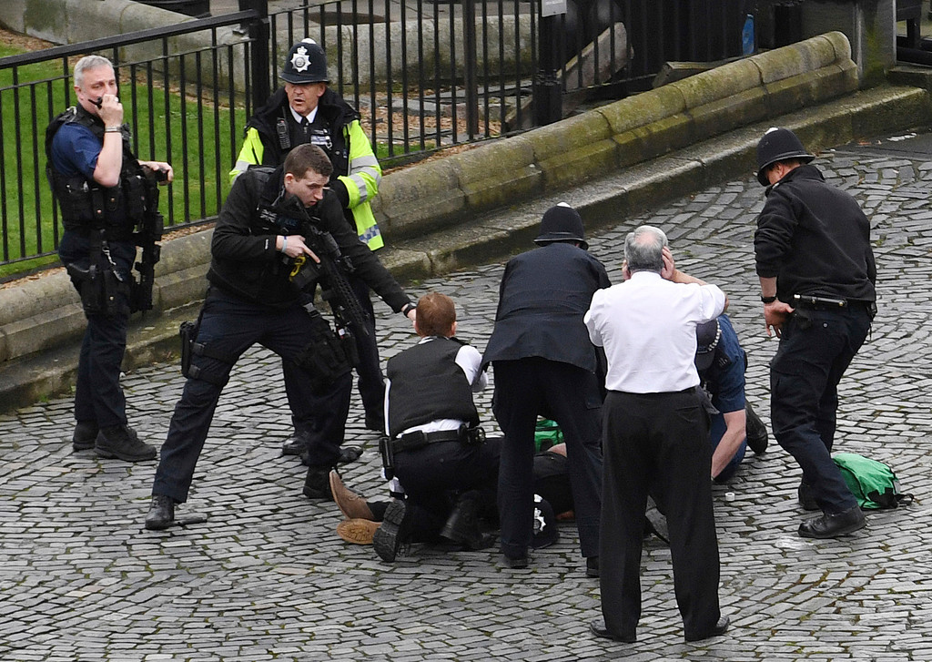 ". A policeman points a gun at a man on the floor as emergency services attend the scene outside the Palace of Westminster, London, Wednesday, March 22, 2017.  London police say they are treating a gun and knife incident at Britain\'s Parliament ""as a terrorist incident until we know otherwise.\"" The Metropolitan Police says in a statement that the incident is ongoing. It is urging people to stay away from the area. Officials say a man with a knife attacked a police officer at Parliament and was shot by officers. Nearby, witnesses say a vehicle struck several people on the Westminster Bridge.  (Stefan Rousseau/PA via AP)."